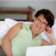 Woman laying in bed with laptop — Stock Photo