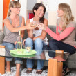 Young women drinking wine on a sofa — Stock Photo