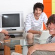 Stock Photo: Housemates relaxing together in their sitting room