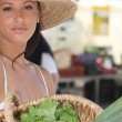 Summery woman in a straw hat holding a basket of market produce — Stock Photo