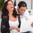 Couple laughing at their laptop - Stock Photo