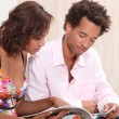Stock Photo: Couple reading a brochure together