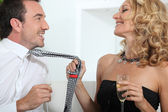 Woman drinking champagne whilst grabbing mans tie — Stock Photo