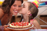Daughter kissing mommy at birthday party — Stock Photo