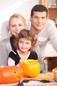Little girl with parents preparing pumpkin for Halloween — 图库照片