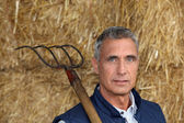 Farmer holding a pitchfork — Stock Photo