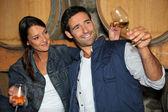 Uśmiechnięty mężczyzna i kobieta, degustacja wina w piwnicy — Zdjęcie stockowe
