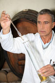 Man testing brandy in a cellar — Stock Photo
