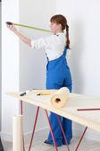 Female decorator measuring wall — Stock Photo
