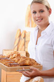 Young female baker with croissants and pain au chocolats — Stockfoto