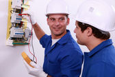 Electrical safety inspectors verifying central fuse box — Stok fotoğraf