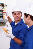 Two electricians testing fuse box — Stock Photo