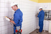 Workteam installing electrics in a tiled room — Stock Photo