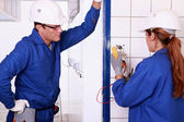Male electrician supervising female apprentice — Stock Photo