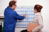 Factory worker showing the schedule to the manager — Stock Photo