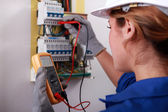 Female electrician taking reading from fuse box — Stock Photo