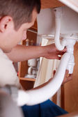 Plumber fixing a sink — Stock Photo