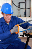 Plumber cutting length of plastic pipe — Stock Photo