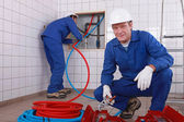 Two plumbers working, one plumber is connecting pipes — Stock Photo
