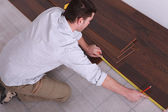 Man measuring wooden flooring — Stock Photo