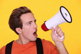 Young man hollering into a megaphone — Stock Photo