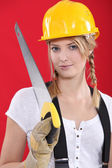 Woman with a hardhat and handsaw — Stock Photo
