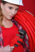 Craftswoman holding a spanner and a hose — Stock Photo