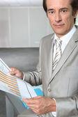 Businessman reading charts — Stock Photo