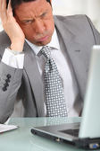 Perplexed man in suit staring at laptop computer — Stock Photo