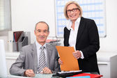 Older couple working in an office — Stock Photo