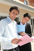 Realty promoters standing in front of a house — Stock Photo