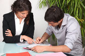 Businesswoman helping her client fill in paperwork — Stock Photo