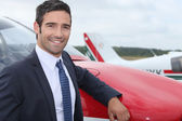 Young businessman standing in front of an airplane — Stock Photo