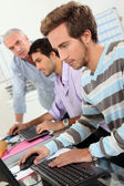 Young men using computers — Stock Photo