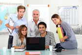 Young team of sitting around a laptop with an older guy — Stockfoto