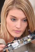 Vrouwelijke technicus kijken naar een elektronische schakeling — Stockfoto
