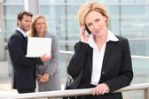 Businesswoman talking on cellphone in front of office building — Stock Photo