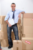 Courrier stood by stacked boxes — Stock Photo