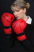 Female office worker wearing boxing gloves — Stock Photo