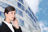 Smart businesswoman making call outdoors near building — Stock Photo