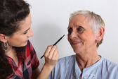 Young woman applying makeup to an elderly lady — Stock Photo
