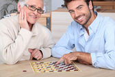 Young man playing game with elderly woman — Stock Photo