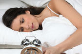 Woman looking her alarm clock — Stock Photo