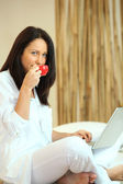 Mature woman drinking her coffee and sending mails — Stock Photo