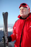 Older man on a mountain with skis — Stock Photo