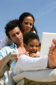 Man, woman and little boy using laptop on a deckchair — Stock Photo