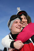 Young couple laughing on the ski slopes — Stock Photo