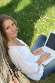 冲浪互联网的一个公共公园的女人 — 图库照片