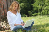 Blond woman sat by tree with laptop computer — Стоковое фото