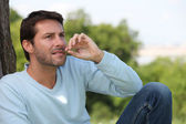 Man chewing a blade of grass in the park — Stock Photo